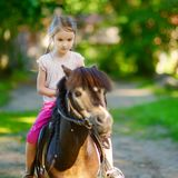 adorable-little-girl-riding-pony-summer-48391984